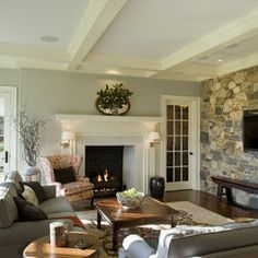 Love that the TV is not above the fireplace, but both are still focal points of the room. And the stone wall is AWESOME!