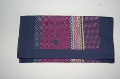Cartera de mano azul marino con doble tela estampada en tonos rosas y cierre de imán. Medidas aprox: 26x13cm. P.V.P: 25€