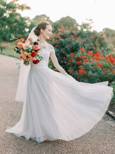 Fall botanic garden wedding with colorful flowers by Wild Fleurette, Virginia & destination wedding and event florist, seasonal autumn bridal bouquet in cream, orange , gold, red, peach, pink and burgundy featuring dahlias, garden roses, honeysuckle, and cosmos, lush and gathered hand tied bouquet, groom in blue suit | Madeleine Deighan Photography | Venue | Lewis Ginter Botanical Garden | Florals | Wild Fleurette | Dress | Here and Now Bridal | HMUA | Anna Breeding Chic Wedding, Floral Wedding, Wedding Styles, Wedding Flowers, Bridal Gowns, Wedding Gowns, Destination Wedding, Wedding Planning, Bridal Bouquet Fall