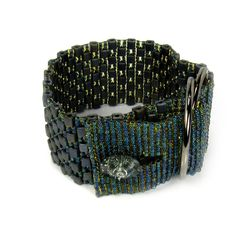 We have created this stunning statement cuff bracelet using Japanese Miyuki Glass Beads in dark French Navy with light rainbow matt finish.  The bracelet has been woven by hand and is finished with a dark blue / charcoal grey Swarovski Crystal button and gold tone buckle rings.  This bracelet will comfortably fit a 7.5 inch (19cm) wrist and is 3.3cm in width.