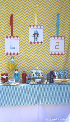 """All little boys love robots and I tried to create this one with a modern twist to a classic theme. We added vintage antique robots collected by Logan's dad to the dessert table and had food to resemble """"robot"""" parts. Red licorice wheels, gumballs, cosmic cookies and more for all to enjoy! Logan's favorite food is french fries, so I created custom french frie cones to match the table fabric. We created arts and crafts projects using robot cut outs. The kids had fun gluing and glittering them…"""