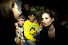 UNHCR Special Envoy Angelina Jolie talks to a Syrian refugee who had just crossed into Jordan with the sound of gunfire coming from the Syrian side. Some 200 refugees made the dangerous crossing on the night that Jolie visited. © UNHCR/J.Tanner