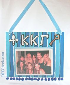 KKG Kappa Kappa Gamma painted canvas.  Made with stencils and other supplies from DIYGreek.com.  Custom Stencils give such a professional finish.  On this, I used half of a photo album from the dollar store, covered the edge in ribbon and glued to the canvas.  The Canvas comes  pre-punched  to make it easy to thread the ribbon.