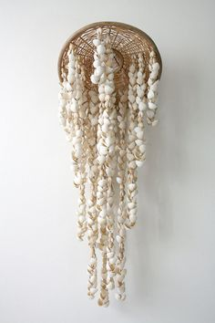 sea shell mobile hanging from a wicker plate!