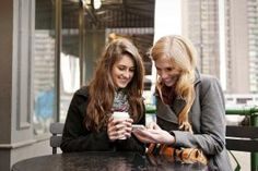 Smiling Young Women Looking At Cell Phone At Cafe - undefined