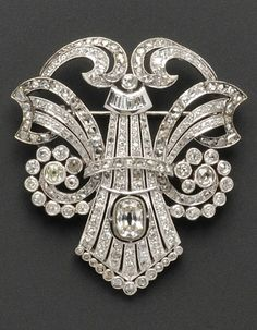 Platinum and Diamond Brooch, bezel-set with a cushion-cut diamond weighing approx. 0.90 cts., further set with old mine-, old single-, and rose-cut diamond