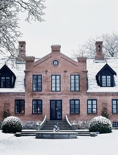 Some sort of Victorian eclectic meets Gothic revival meets English arts & crafts brick home with crenellation, black window casements, and black dormers.