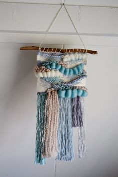 This intricately hand-woven wall tapestry is full of texture and charm. Woven using range of fibres such as hand-dyed merino wool roving, linen and hand-spun wool in a palette of frosty blue, cream, grey and silver, its a unique piece that stands out on the wall! This piece measures approximately 58cm long and 29cm wide. It hangs from a wooden stick found on a canal side walk in Delft, the Dutch town in which this piece was made.
