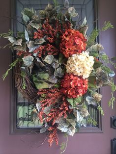 This wreath design features three big vibrant hydrangeas in blazing orange and ivory nestled on a mound of lush greenery and beautiful berries