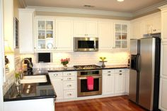 White cabinets, subway tile, black stone countertops and wood floors. Love!