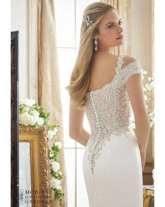 Crystallized embroidery embellishes the bodice and cold shoulder short sleeves of this Mori Lee 2880 Duchess satin wedding dress with trumpet silhouette. This gown showcases a softly scalloped illusion V-neckline and an illusion back accented with covered buttons. The skirt flows smoothly into a chapel train.