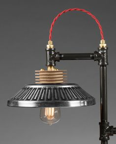 Notice this listing is on hold for Mike. Total before shipping 250.00 - 150.00 paid = 100.00 plus shipping. With steam-punk and industrial design inspirations, this lamp is made of iron pipe fittings that have been painted to protect from rust, brass wire fittings, industrial toggle switch, accented with twisted red wiring, and re-purposed Ford hubcaps that serve as reflectors. The base of the lamp is made red wood and is protected with an oil rubbed finished. The bottom of the wood base has