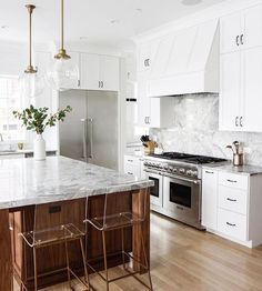 This minimalist kitchen features marble counter tops, gold details, and gorgeous clear barstools