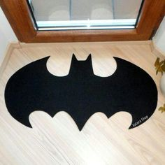 Rug based in a Batman logo. Custom door by Xatara - or just make it yourself with a cardboard stencil. Who doesn't like Batman!