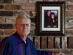 """Cliff Roberts stands next to a portrait with his wife of 67 years, Marcyene, who died about four years ago. They were married three months before the attack on Pearl Harbor. """"I told her I had to go,"""" said Roberts, who served as a gunner on a boat that dropped off soldiers at Normandy on D-Day."""