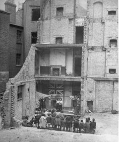 1943 London at War - Aldgate School    1943 - Children in Aldgate using the ruins of a bombed house as a stage for a school play.