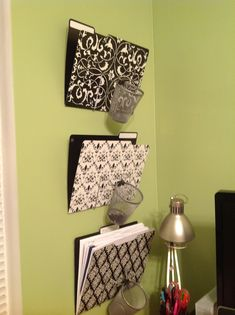 """DIY File Rack: Metal display easels, pencil cups, and butterfly clips from Dollar Tree - total cost $7!  Flip easels upside down and bend """"v"""" as much as possible, clip cup and put in pretty file folders. Attach all with couple small nails to wall."""
