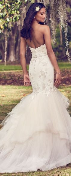 Maggie Sottero - DALINDA, This mermaid wedding dress features a tulle bodice accented in embroidered lace motifs atop a tiered tulle fit-and-flare skirt edged in horsehair. Complete with strapless sweetheart neckline and bead and pearl embellished belt. Lined with shapewear for a figure-flattering fit. Finished with covered buttons over zipper closure.