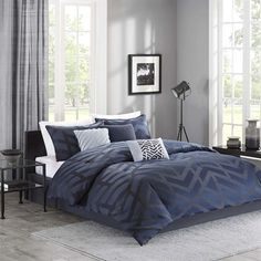 Looking to add a contemporary touch to your room? Then the Chevron Nights 7 Piece Comforter Set by Madison Park is the perfect option! The comforter is made of 100% polyester jacquard and features an oversized geometric design in a medium greyish blue on a solid navy blue ground. The reverse of the comforter, along with the bed skirt, is solid navy blue. Two standard shams and three decorative pillows are also included to add extra comfort and style to this contemporary collection.