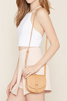 A structured faux leather saddle crossbody with an adjustable shoulder strap and a strappy accent on the snap-magnetic flap top.