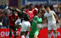 Paul Pogba of Manchester United balances on top of Kyle Bartley of Swansea City as Lukasz Fabianski of Swansea City tries to make a save during the Premier League match between Swansea City and Manchester United at Liberty Stadium on August 19, 2017 in Swansea, Wales.