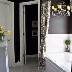 Yellow and grey bathroom color scheme. Love the curtains over the tub and the chandelier.