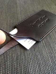 Leather luggage tag with custom stamping and business card slot inside; CREW stamp on reverse side.