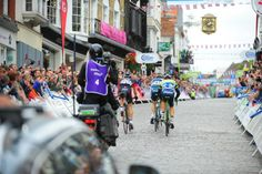 Riders climbing the cobbled High Street of Guildford towards the finish line.