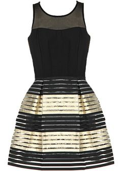 Party Favor Dress: Features a sheer mesh yoke with a subtle sweetheart neckline, solid black bodice with keyhole closure to the back, and a lustrous A-line bandage skirt with gold accent to finish.