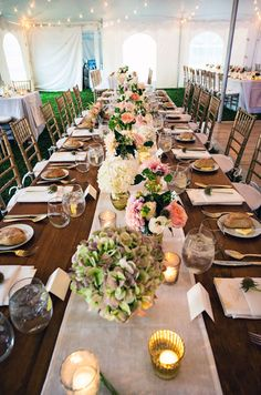A long banquet table is topped with pastel linens and fresh blooms.