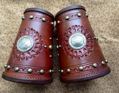 A pair of Cowboy Cuffs, with Concho, Spots and stamping detail, pigskin stitched edge roll and finished in a Medium brown oil finish These cuffs