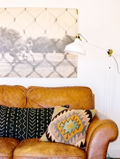 Black and white art above leather sofa, patterned pillows, and modern floor lamp