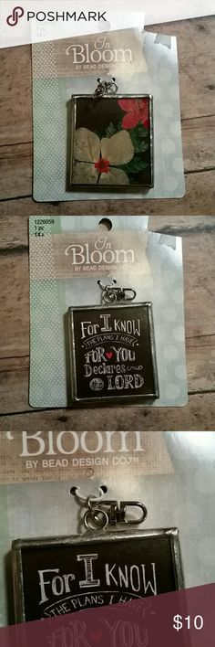 """Double Sided Pendant by In Bloom A double sided pendant that has a beautiful floral design featuring white and red flowers with a black backround. The opposite side reads a comforting, bible quote """"For I know the plans I have for you declared the Lord"""". It is set in a silver framed pendant and ready to be used to add to a chain, fabric, or any medium you choose. In Bloom by Bead Design Co. Jewelry Necklaces"""