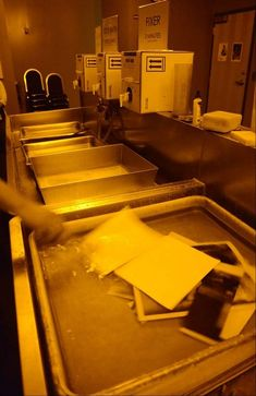 Photography student Charlie Anderson transfers black and white prints from a fixer bath to a wash bath in the ECC darkroom.