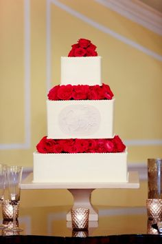 White wedding cake with beautiful red roses.