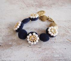 丁寧に縫い付けられたビーズのお花が華やか。 手元をさりげなく華やかに飾ってくれそう。