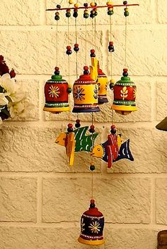 Here, an alternate circular arrangement of hand painted bells and fishes, put together with colourful beads, serves as a decorative wind chime. The terracotta pieces have been painted in acrylic colours and thus are water resistant.   The product is a creation of local artisans of Delhi.