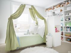 In a Manhattan apartment decorated by David Mann of MR Architecture + Decor, a canopy bed by Anthropologie in a child's bedroom is draped with a Pierre Frey cotton; the side table is by Kartell.