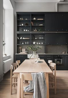 Open plan kitchen / dining room with black cabinets & birch dining table. | Breathtaking Loft - via Coco Lapine Design