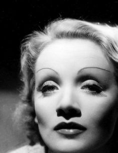 """Marlene Dietrich, 1930s.  Brows: artificial, thin and curved, located high above the eye and elongated Eyes: softly sculpted, creased and lash line defined +false lashes Lips: """"The Rosebud""""; a fuller and more natural version of the """" Bee Stung"""" Cheeks: Blush used to sculpt"""