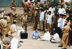 Former Tamil Nadu Chief Minister Muthuvel Karunanidhi, wearing dark glasses, sits on the ground with other unidentified supporters in front of the Madras central jail after his arrest from his residence in Madras, India, Saturday, June 30, 2001.
