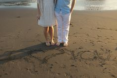 Writing in the sand engagement photo  Sara Faith Photography