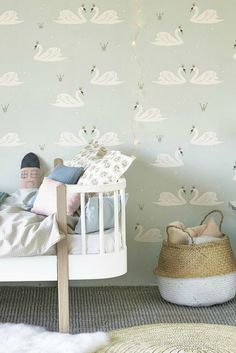 A delightful nursery style motif wallpaper design by Hibou Home with swans, crowns and a sprinkling of stars. Available in two colours this is the mint green.