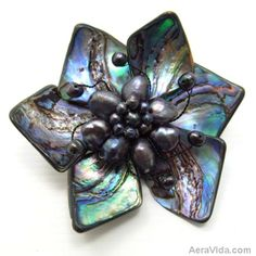 Add a floral essence to your outfit with this amazing piece handmade in Thailand. This pin or brooch features genuine abalone shells with freshwater black pearl accents. SKU:  OP-0006-ABL