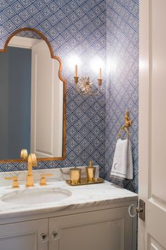 Beautiful tile pattern and gold bathroom fixtures.