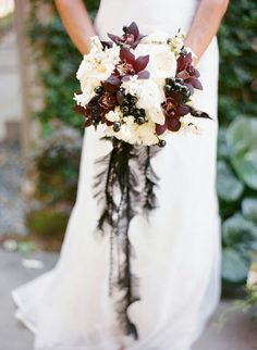 Very Elegant Bridal Bouquet Comprised Of: White English Garden Roses, White Ranunculus, Additional White Florals, Burgundy Cymbidium Orchids, White Snowberry & Dark Berries