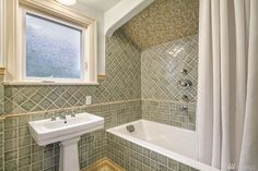 Love the wood work around the window. Sink not bad and nice that they kept the tub alcove. Who talked them into that hideous tile job? Other baths in same house are similarly horribilified. 1919 Queen Anne Hill.