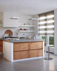 Cucina moderna in muratura con isola centrale - pareti bianche, pavimenti e top in cemento, cassetti in legno chiaro, - isola centrale