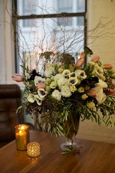 Clusters of Calla, Ranunculus, Tulips, Spray Roses, Queen Anne's Lace (Chocolate), Privet Berry and Olive Branches.
