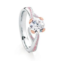 Elegant engagement ring with pink side stones that draw the eye to the center diamond. Marshall Jewelry